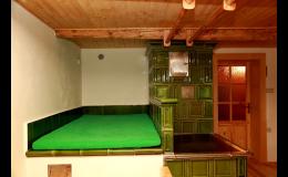 Společenská místnost s kachlovými kamny v Chalupě Sněženka